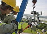 Hydro-Québec line workers install the LineScout on a transmission line in preparation for an inspection.